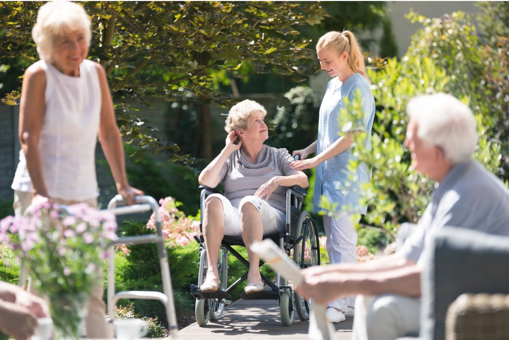 Aged care residents with nurse in garden
