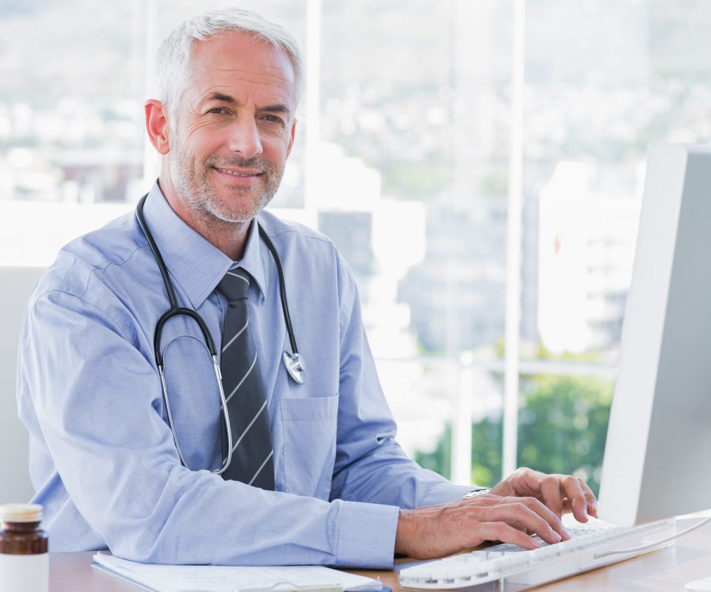 Male GP at desk in front of computer
