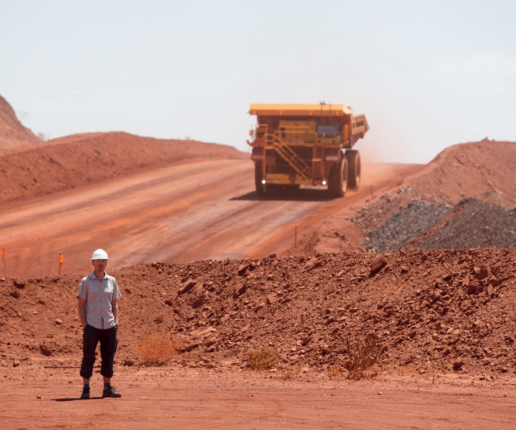 Worker standing in foreground of mine site with mining vehicle in background