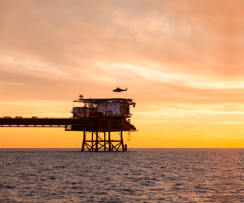 Offshore oil rig with helicopter landing at sunset