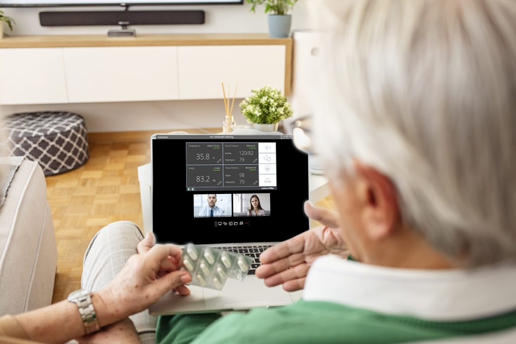 Senior couple on online therapy. They are sitting on the sofa in the living room, having a video call with a doctor. Senior couple consulting with their doctor. Health care and modern technology for the elderly.